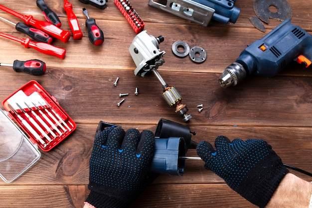 マスターは壊れた電気機器を修理します:木製のテーブルのドリル、カッター。電動工具修理店 Premium写真