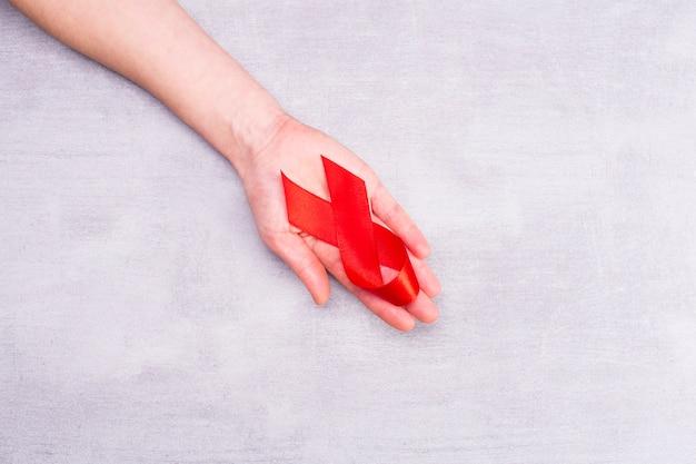 Красная лента со спидом на женской руке в поддержку всемирного дня борьбы со спидом Premium Фотографии
