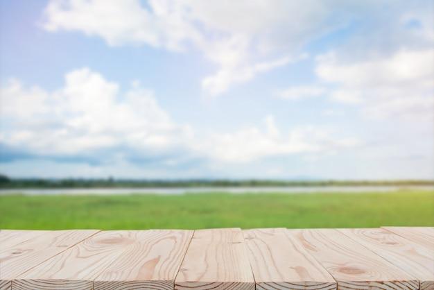 空の木の板テーブルの上にぼやけている青い空と川の背景。コピースペース Premium写真