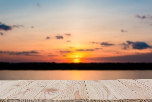 空の木の板テーブルぼやけ夕日と湖の背景の上。 Premium写真