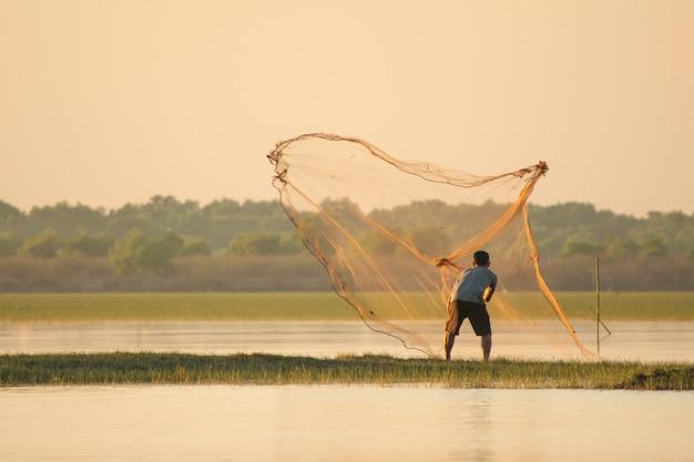 漁師は湖に網を投げる Premium写真