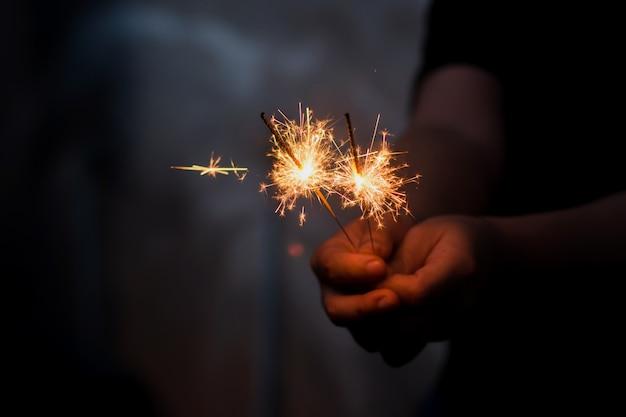 燃える線香花火を持つ女性の手 Premium写真