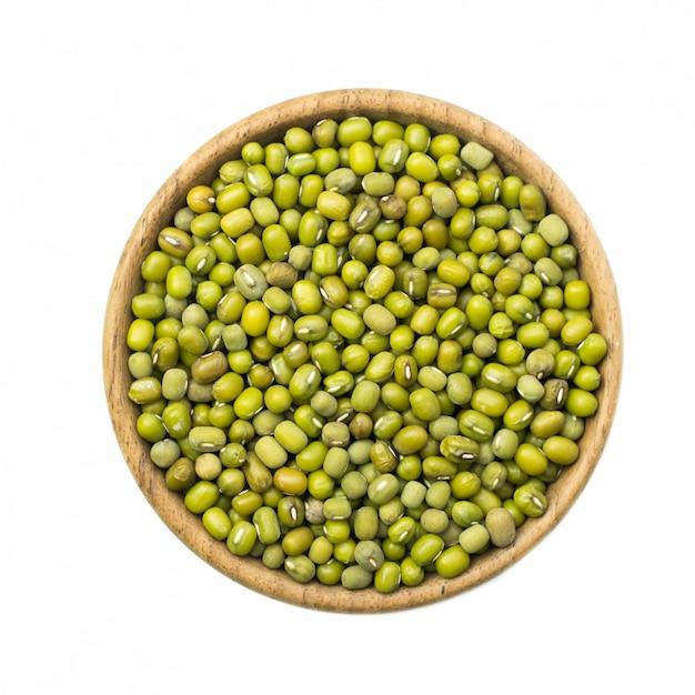 白い背景で隔離の木製のボウルに緑豆 Premium写真