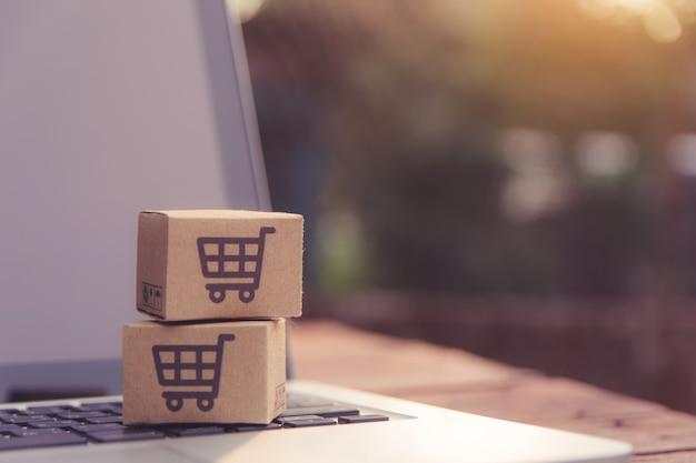 オンラインショッピング - ノートパソコンのキーボードにショッピングカートのロゴが入った紙パックまたは小包。オンラインウェブ上のショッピングサービスと宅配便を提供しています。 Premium写真