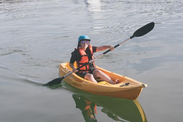 オレンジ色のライフジャケット、湖でのカヤックの若い女性。 Premium写真