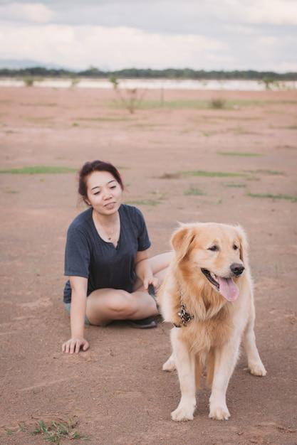屋外で遊ぶ彼女のゴールデン・リトリーバー犬を持つ女性 Premium写真