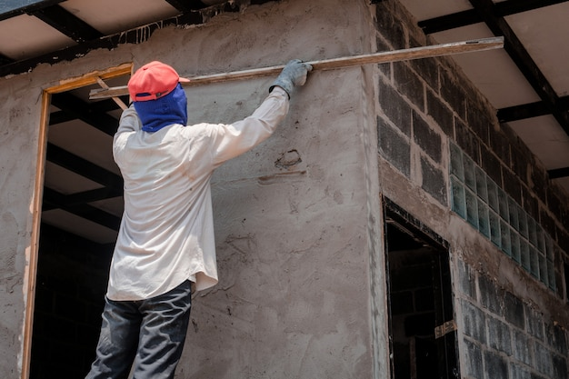 Строители оштукатуривают стены здания цементной штукатуркой Premium Фотографии