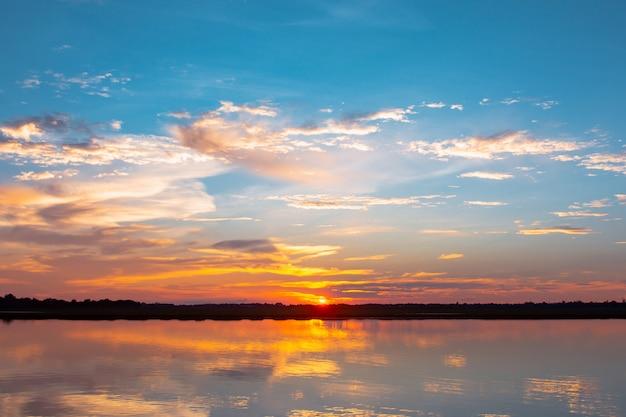 Закат отражение лагуны. красивый закат за облаками и голубое небо над лагуны. резкое небо с облаками на закате Premium Фотографии