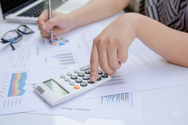 オフィスで財務を行うと紙のグラフデータに電卓を使用して女性を閉じます。 Premium写真