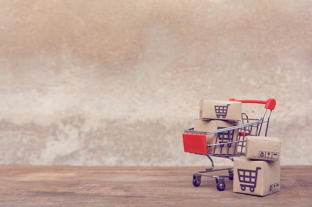 カートンまたは茶色の木製テーブルの上のショッピングカートの紙箱。 Premium写真