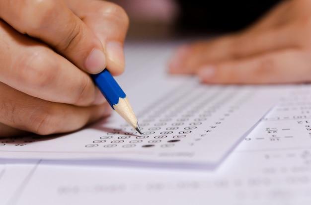 Студенты рука карандашом писать выбранный выбор на листах ответов Premium Фотографии