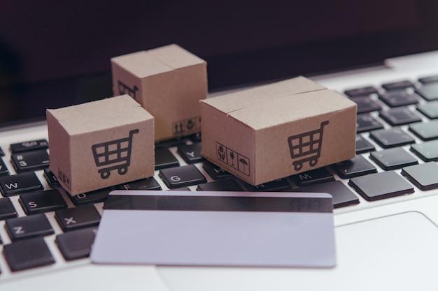 Покупки онлайн - бумажные коробки или посылки с логотипом корзины покупок и кредитной картой на клавиатуре ноутбука. служба покупок в интернете и предлагает доставку на дом. Premium Фотографии