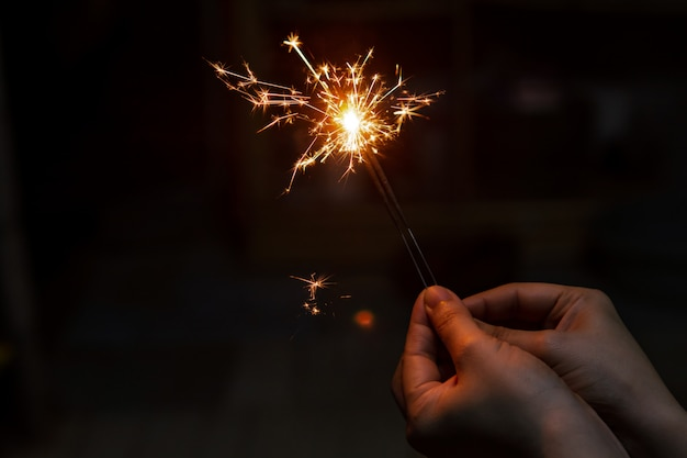 Женская рука держит горящий бенгальский огонь Premium Фотографии