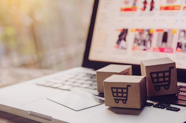 Бумажные коробки с логотипом корзины покупок и кредитной карты на клавиатуре ноутбука. Premium Фотографии