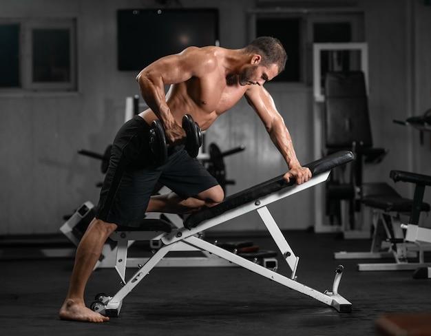 男はジムで訓練します。アスレチック男、彼の上腕二頭筋をポンピング、ダンベルトレーニング Premium写真