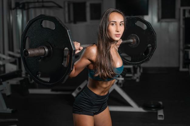 足をポンピング、バーベルの女性トレーニング Premium写真