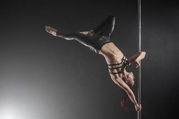 パイロンを持つ男。黒の上で踊って男性ポールダンサー Premium写真