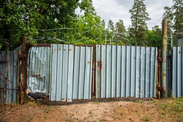 有刺鉄線で覆われた古い金属製のゲート、施錠された私有財産 Premium写真