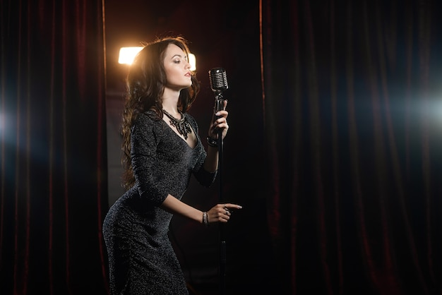 コンサートホールのマイクで歌っている黒のドレスで美しい少女 Premium写真