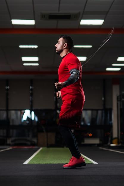 ジムでロープでジャンプする大きな筋肉でハンサム Premium写真