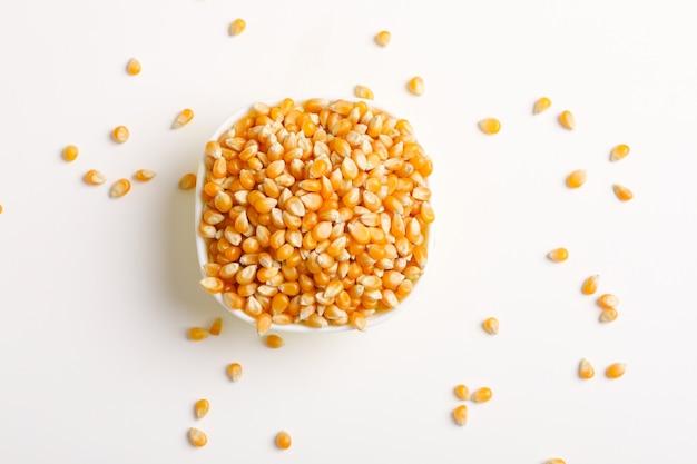 白のボウルに乾燥したトウモロコシの種子 Premium写真
