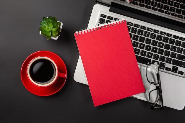 オフィスの黒いテーブルの上のノートパソコンとコーヒーカップの上の空白のメモ帳 Premium写真