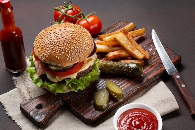 牛肉、トマト、レタス、チーズ、タマネギ、きゅうり、フライドポテトの食材を使った自家製ハンバーグ Premium写真
