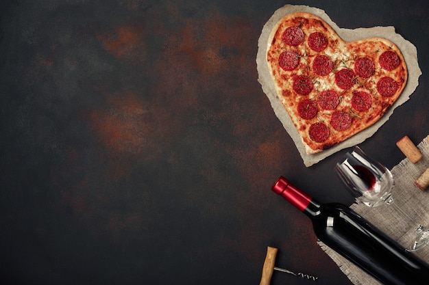 ハート型のピザとモッツァレラチーズ、ワインとワイングラスでソーセージ。さびた背景にバレンタインの日グリーティングカード Premium写真