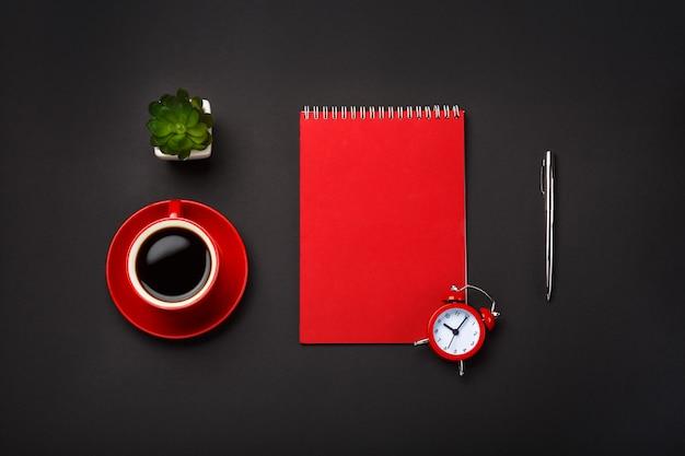黒の背景赤コーヒーカップメモ帳目覚まし時計花空スペースデスクトップ Premium写真