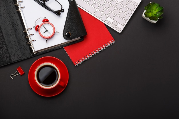 黒背景赤コーヒーカップメモ帳目覚まし時計花日記スコアキーボード空スペースデスクトップ Premium写真