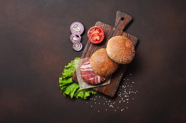 ハンバーガー食材の生のカツレツ、トマト、レタス、パン、チーズ、キュウリ、さびた背景にタマネギ Premium写真