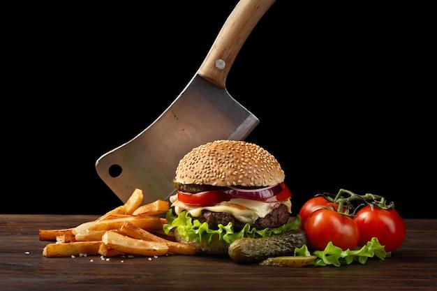 牛肉、トマト、レタス、チーズ、タマネギ、木製テーブルのフライドポテトと自家製ハンバーグのクローズアップ。ハンバーガーにナイフを刺しました。暗い背景にファーストフード Premium写真