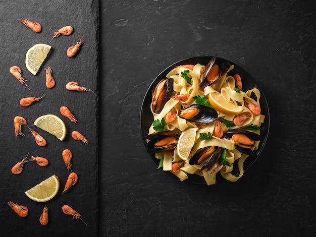新鮮な生のエビまたはスパイスとレモンの暗い石の背景にスレートの石で煮赤エビ Premium写真