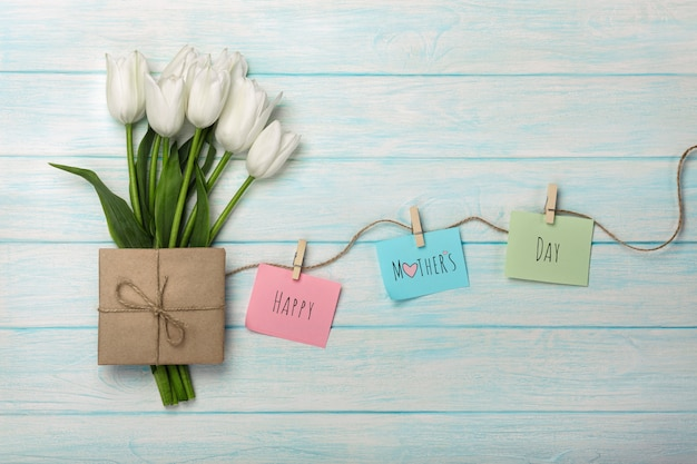 白いチューリップの花束とロープと青い木の板に洗濯はさみが付いたカラーステッカー付き封筒。母の日 Premium写真