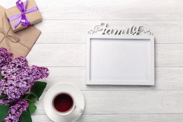 ホワイトボードに碑文、紅茶のカップ、ギフトボックス、クラフト封筒のホワイトフレームとライラックの花束 Premium写真