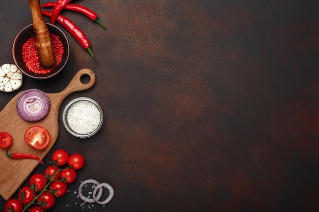 さびた茶色の背景にチェリートマト、ローズマリー、ニンニク、赤ピーマン、玉ねぎ、塩、スパイスモルタルからまな板の上の製品のセット Premium写真