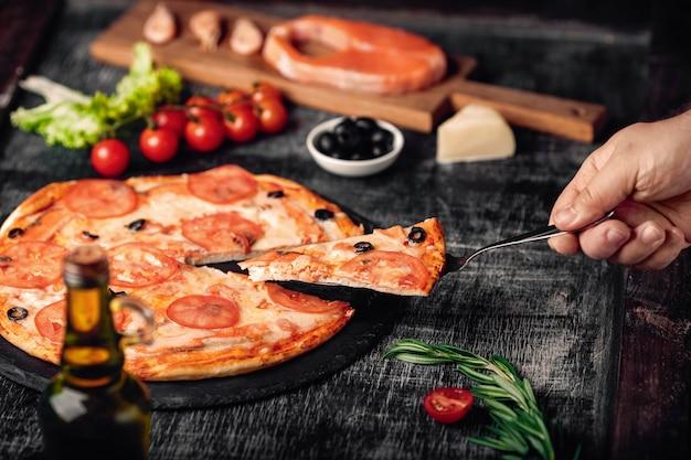 チョークボード上のチーズ、マス、トマト、オリーブ、エビと手でピザのスライスをスライスしました。 Premium写真