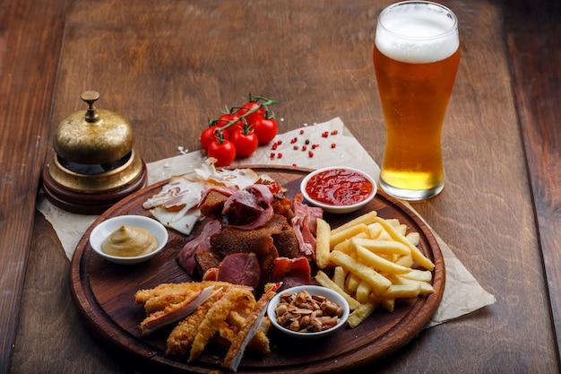 ビールやアルコールのスナック、豚肉のスモークミート、フライドポテト、フライパン、カニの棒、ナッツなど Premium写真