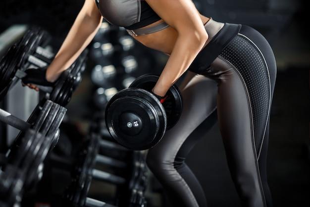 スリムなボディービルダーの女の子は、ジムでトレーニングしながら、鏡の前に立っている重いダンベルを持ち上げます。スポーツコンセプト、脂肪燃焼、そして健康的なライフスタイル Premium写真