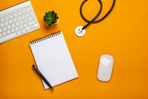 聴診器キーボードのメモ帳とペンを持つ医師のテーブルの上から見る Premium写真