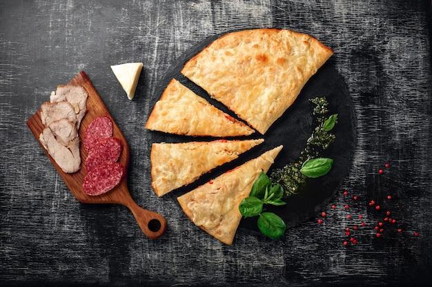 石とダークウッドの傷の背景上の成分と伝統的なイタリアのピザカルゾーネ Premium写真