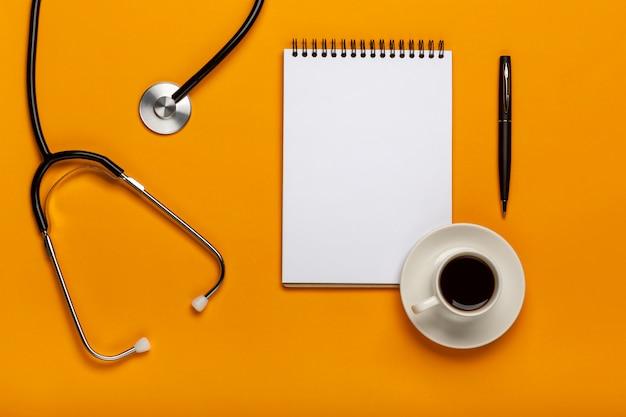 Вид сверху стол врача с стетоскоп, кофе и чистый лист бумаги в буфер обмена с ручкой Premium Фотографии