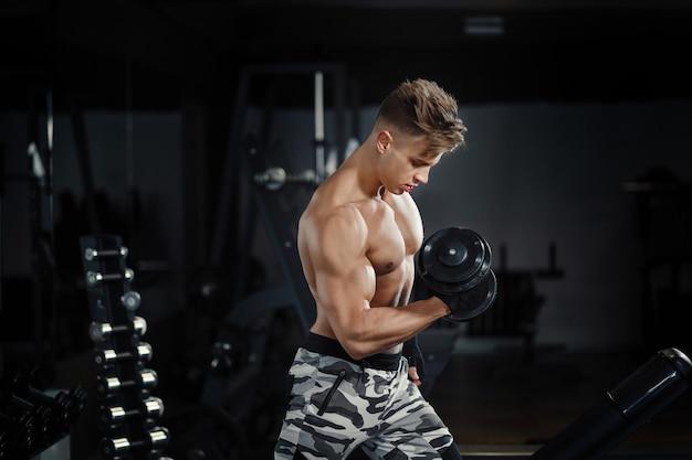 Молодая взрослая женщина тренируясь в спортзале, делая скручиваемости бицепса с помощью ее личного тренера Premium Фотографии