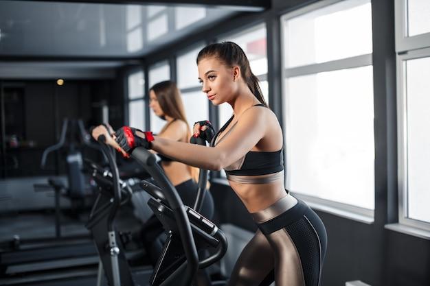 魅力的な若いスポーツ女性はジムでエクササイズします。トレッドミルでカーディオトレーニングをしています。トレッドミルで走る Premium写真
