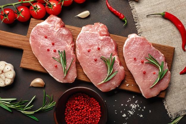 さびた茶色の背景にチェリートマト、ローズマリー、ニンニク、コショウ、塩、スパイスモルタルでまな板の上の生豚肉ステーキの部分 Premium写真