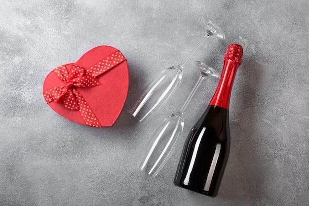 シャンパンのボトルとバレンタインカード、ハートの形のチョコレートの箱とグラス。 Premium写真