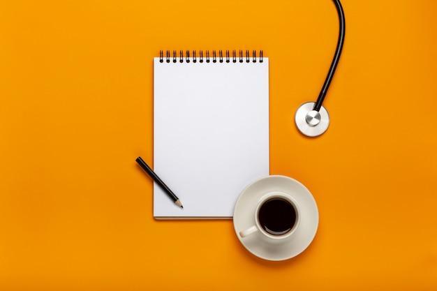 ペンでクリップボードに聴診器、コーヒー、空白の紙をドクターデスクテーブルの上から見る Premium写真