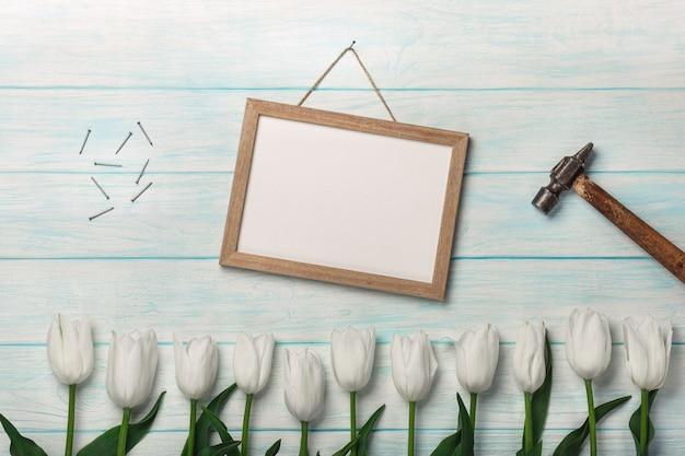 青い板に白いチューリップ、チョークボード、ハンマーと金属の釘。母の日 Premium写真