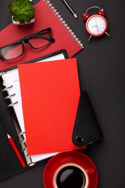 赤いコーヒーカップ、メモ帳、目覚まし時計、トップビューで花と黒の背景 Premium写真