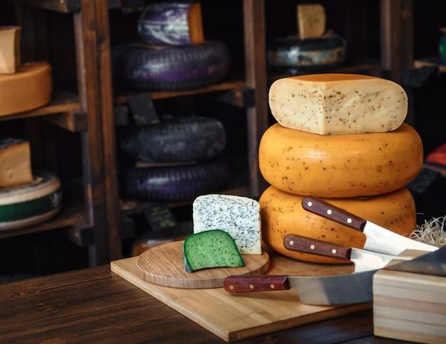 ナイフでテーブルの上の金型とおいしいチーズブルーグリーンバイオレットチーズの様々な種類の木の板 Premium写真
